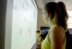 Estudiante en pizarrón interactivo