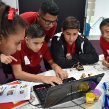 Jóvenes trabajando en equipo frente a computadora