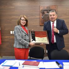 Rectora recibe placa de manos del director de GRANA