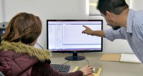 Profesor y estudiante frente a una computadora