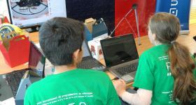 Niños trabajando frente a computadora de escritorio, en el proyecto R2T2