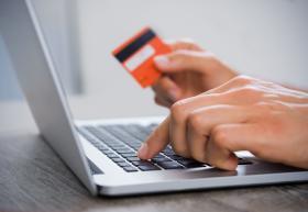 Persona frente a computadora con tarjeta bancaria en mano