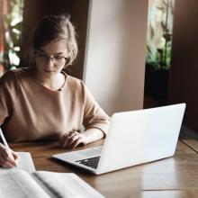 Estudiante frente a computadora, tomando notas