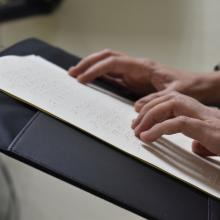 Manos de persona con discapacidad visual leyendo braile
