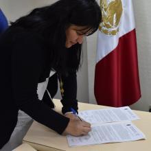 Egresada firmando el acta de titulación